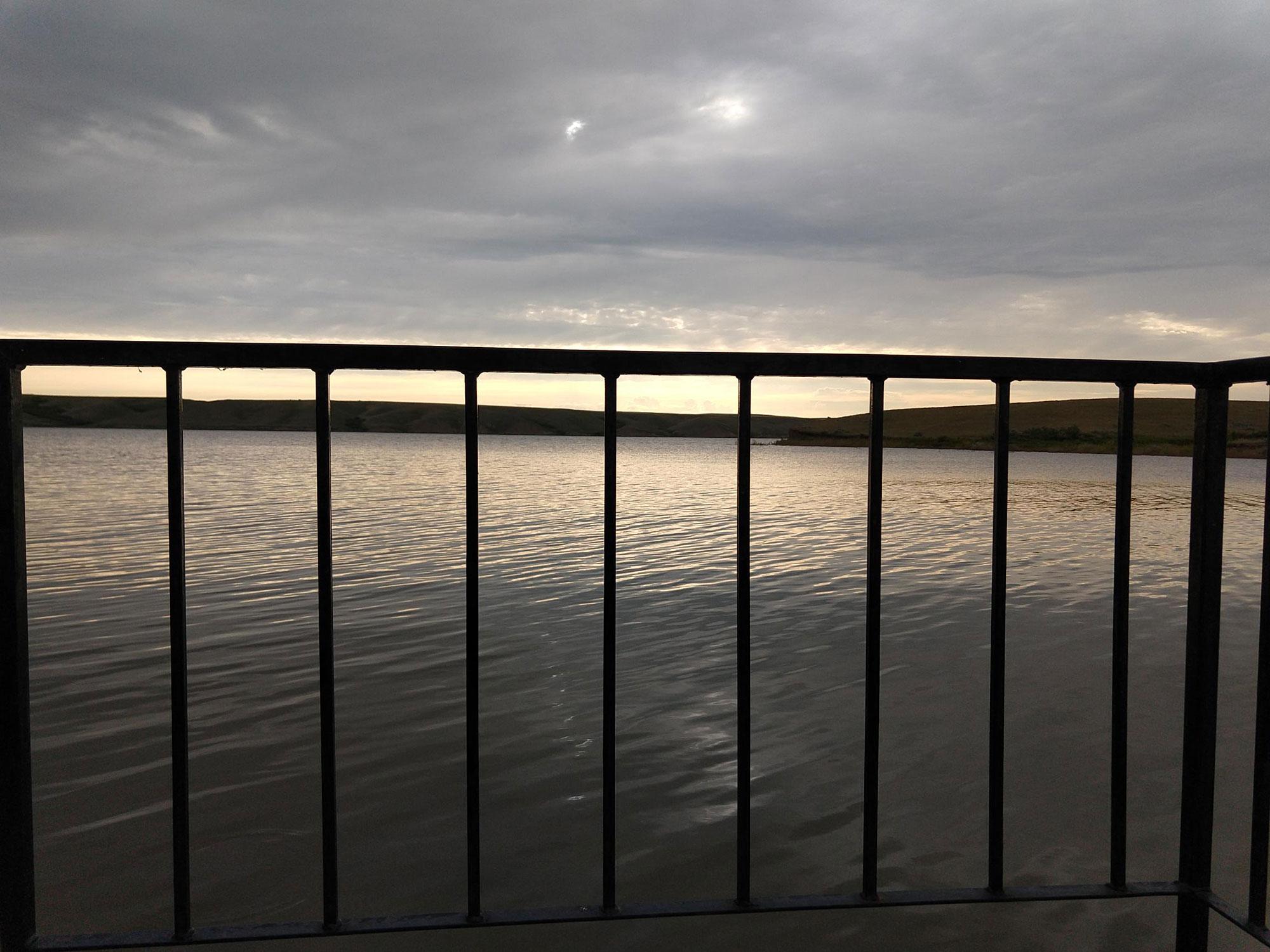 Blick über den See durch die Schiffsreling bei Sonnenuntergang
